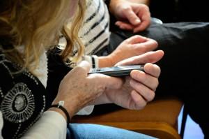 Foto af deltager, der undersøger en mobiltelefon.