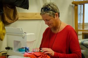 Foto af kvinde, der arbejder ved en symaskine.