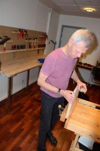 Foto af blind mand, der arbejder med træ.