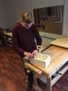 Foto af blind kvinde, der arbejder med træ på værkstedet.