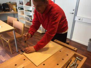 Foto af ung mand, der arbejder med træ.