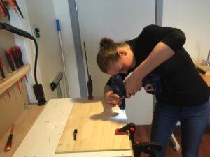 Foto af ung kvinde, der står bøjet over arbejdsbordet med værktøj i hænderne.